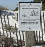 Florida Beach Dune Restoration Sign. A fence and sign warn visitors to stay off the dunes due to beach dune restoration in progress at Camp Helen State Park Royalty Free Stock Images