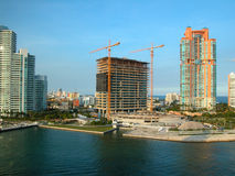 Florida Coast Construction Site. A picture of a waterfront real estate development, with most of the floors already built. Two cranes flank the work-site while royalty free stock photo