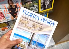 Florida Design magazine in a hand. MIAMI, USA - AUGUST 22, 2018: Florida Design magazine in a hand over a stack of magazines royalty free stock photography