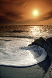 Florida Gulf Coast Sunset With Large Wave and Warm Sky. This large, circular wave wraps around the remains of an old lighthouse foundation creating a calm Royalty Free Stock Image
