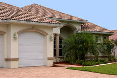 Florida home. A generic one story florida home with garage, palm trees and a clear blue sky stock photos