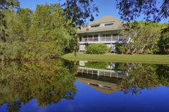 Florida home with private pond reflection. Blue sky reflection on a private pond of a secluded residential home on Sanibel Island Florida surrounded with Royalty Free Stock Images