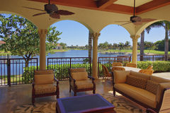 Florida luxury home deck area with water view. Florida luxury home deck with pillars, protected interior quality furniture, decorative fans, and water view of Royalty Free Stock Photography