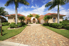 Florida luxury home with paver block driveway. Florida luxury home in private community with decorative multi-color paver block driveway, palm trees, and Stock Images