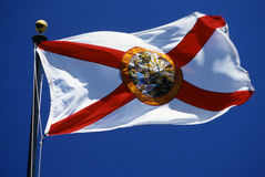Florida State Flag. This is the Florida State Flag waving in the wind. It is on a flagpole against a blue sky. It has a red cross against a white background with Stock Photography