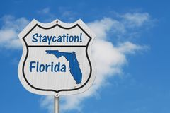 Florida Staycation Highway Sign with sky. Florida Staycation Highway Sign, Florida map and text Staycation on a highway sign with sky background royalty free stock photo