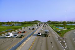 Florida Turnpike. Evening rush hour traffic is moving smoothly on the Florida Turnpike facing south at Pompano Beach, Florida with clear blue sky overhead Stock Photography