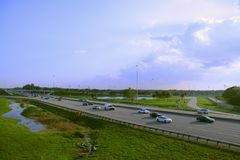 Florida Turnpike. Rush hour traffic is moving smoothly on the Florida Turnpike, facing southwest at Pompano Beach, Florida in the evening with partly cloudy sky Royalty Free Stock Photo