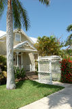 Florida typical. An older clapboard house with a trellis arch over the walkway and a palm tree in the yard is typical of southwest florida stock photo