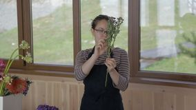 Florist in an apron cleans dry flower from leaves for bouquet. stock footage