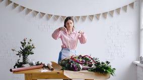 Florist arranging bouquet in flower shop, tying ribbon. 4k stock photography