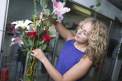 Florist Arranging Flowers In Vase. Young female florist arranging flowers in vase stock images