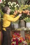 Florist arranging fresh flowers stock image