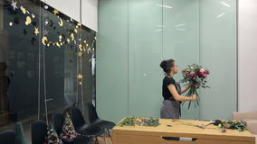 Florist Asian collects a bunch of red, pink and white roses in a large room. Lady in the studio putting the branch of one plant to the composition to produce a stock video footage