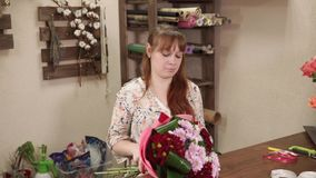 Florist assembles beautiful bouquet. Beautiful blonde woman is decorating bouquet in a flower shop alone. She is focused and concentrated stock video