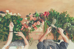Florist and assistant in flower shop delivery make rose bouquet, table top view royalty free stock photo