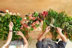 Florist and assistant in flower shop delivery make rose bouquet, table top view stock images