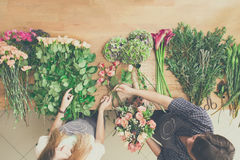 Florist and assistant in flower shop delivery make rose bouquet, table top view stock image