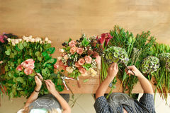 Florist and assistant in flower shop delivery make rose bouquet, table top view royalty free stock image