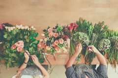 Florist and assistant in flower shop delivery make rose bouquet, table top view stock photos