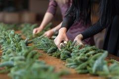 Florist bei der Arbeit: Frau übergibt die Herstellung der Weihnachtsdekorationsgirlande der Tanne Guten Rutsch ins Neue Jahr-Aben stockfotos