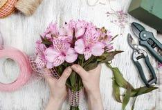 Florist bei der Arbeit: Frau, die Blumenstrauß von Alstroemeriablumen vereinbart Stockbild