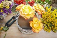 Florist bei der Arbeit: Frau, die Blumenstrauß von den orange Rosen und vom Herbst macht Stockbild