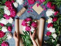 Florist bei der Arbeit: hübsche Frau, die Sommerblumenstrauß von den Pfingstrosen auf einem arbeitenden grauen Schreibtisch macht Stockfotografie