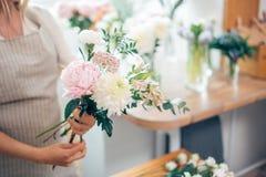 Florist bei der Arbeit: recht junge blonde Frau, die Blumenstrauß von den verschiedenen Blumen macht Lizenzfreie Stockbilder