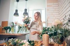 Florist bei der Arbeit: recht junge blonde Frau, die Blumenstrauß von den verschiedenen Blumen macht Stockbild