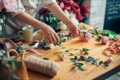 Florist bei der Arbeit: recht junge blonde Frau, die Blumenstrauß von den verschiedenen Blumen macht Lizenzfreie Stockfotos