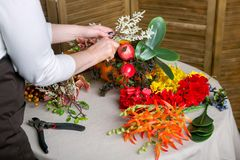 Florist bei der Arbeit: Wie man ein Danksagungsmittelstück mit großem Kürbis und Blumenstrauß von Blumen macht Schritt für Schrit stockbilder