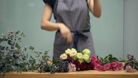 Florist bereitet vor sich, frische Blumen zu schneiden für ein Mischblumenstraußvereinbaren stock video