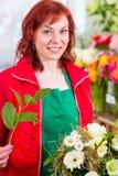 Florist binding flower bunch in shop Stock Images