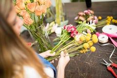 Florist choosing flowers for an arrangement stock photography