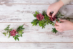 Florist collects bouquet. Florist gathers a bouquet with their hands  on vintage background Royalty Free Stock Image