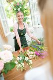 Florist with cut flowers in front Royalty Free Stock Photos