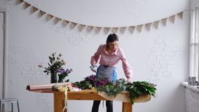 Florist cuts roses in flower shop royalty free stock photography
