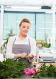 Florist Cutting Stem On Rose At Counter In Flower Stockfoto