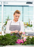 Florist Cutting Stem On Rose At Counter In Flower Stockfotos