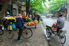 A Florist and a cyclist are waiting for their costumers on a pavement Royalty Free Stock Images