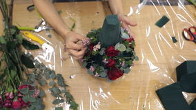 Florist decorates bouquet by greens and beautiful natural flowers. Cone-shaped composition consists of ruby roses, small branches with foliage, wonderful stock footage