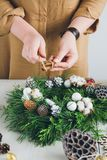 Florist decorator making Christmas wreath. Handmade on a white table. Women`s hobby. Preparations for the holidays concept stock image