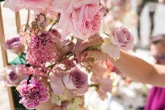 Florist decorator workflow, Woman hands decorating wedding arch with fresh flowers. Event decoration with fresh flowers.  stock images