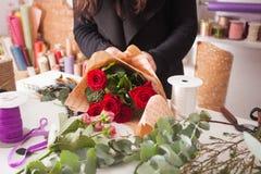 Florist, der Blumenstrauß von den roten Rosen macht Lizenzfreie Stockbilder
