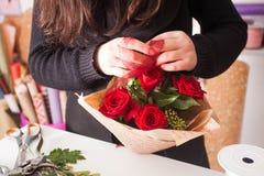 Florist, der Blumenstrauß von den roten Rosen macht Lizenzfreie Stockfotos