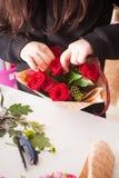 Florist, der Blumenstrauß von den roten Rosen macht Stockfotografie