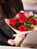 Florist, der Blumenstrauß von den roten Rosen macht Stockfoto