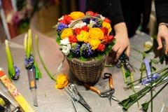 Florist, der eine schöne Blumenzusammensetzung in einem Weidenkorb macht Stockfotos