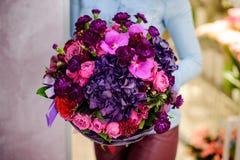 Florist, der einen herrlichen purpurroten Blumenstrauß von Blumen hält Stockfotografie